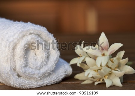 White towel and a flower on a teak table - stock photo