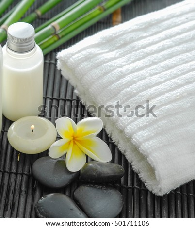 White towel and stones and flower ,grove on bamboo mat