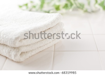 White towels and green on white tile - stock photo