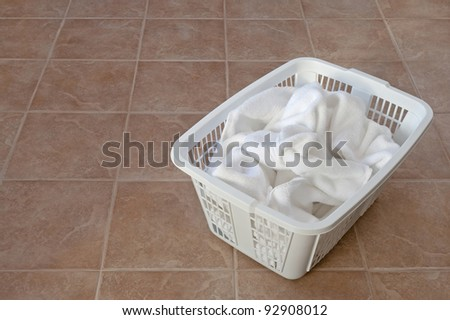 White towels in a laundry basket on ceramic floor, in a laundry room or bathroom. - stock photo
