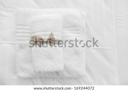 White towels with grey ribbon folded on white sheets - stock photo