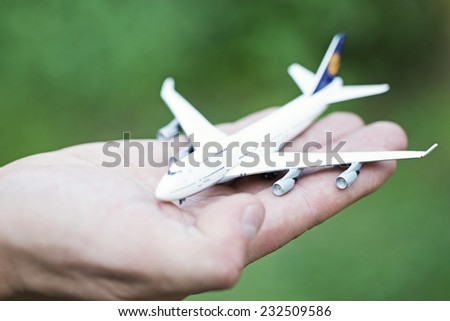 white toy airplane on palm - stock photo