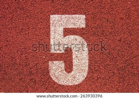 White track number on red rubber racetrack, texture of running racetracks in small stadium - stock photo