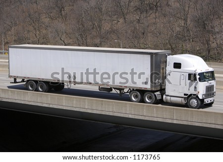 White Tractor Trailer Semi Truck on the Highway with Blank Trailer - stock photo