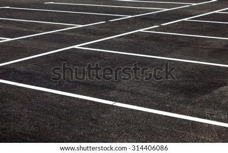 White traffic markings on a gray asphalt parking lot - stock photo