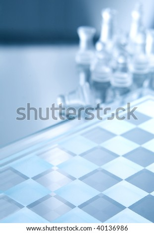 White transparent pieces of chess on chess board made of glass. All in blue ambient light - stock photo