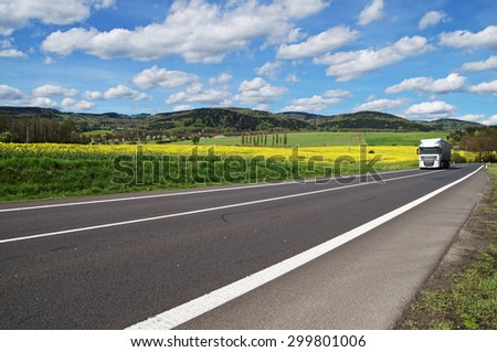 White truck arrives from a distance on an asphalt road between the yellow flowering rapeseed field in countryside. Wooded mountains in the background. Blue sky with white clouds. - stock photo