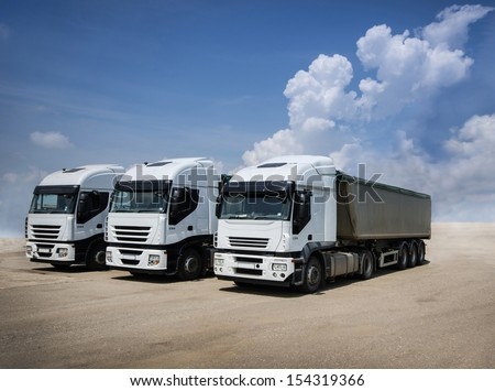 White trucks parked on a sand ground - stock photo