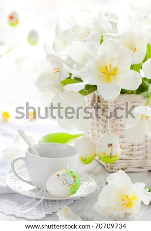 white tulips in a basket,easter eggs and cup of tea - stock photo