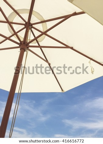 White umbrella and blue sky background. - stock photo