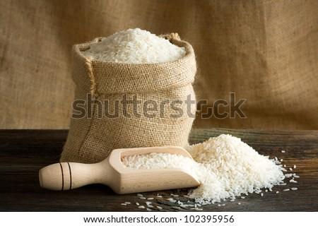 White uncooked rice in burlap bag - stock photo