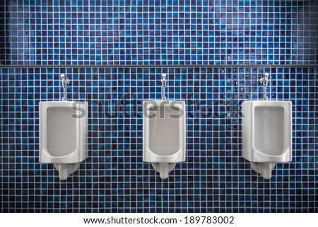 white urinal in men public toilet with blue wall tile - stock photo