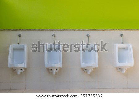 white urinals in men's bathroom, design of white ceramic urinals for men in toilet room - stock photo