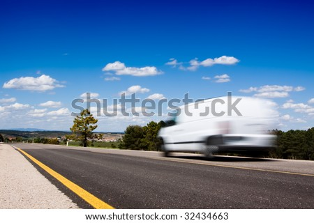 White van in a country road with some trees and a great blue sky above - stock photo