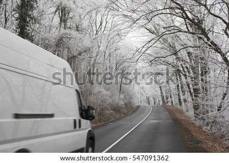 White van transporting on winter road