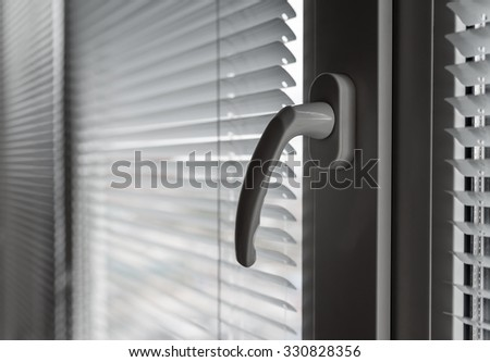 White venetian blinds. Selective focus on the window handle. - stock photo