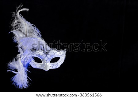 white venetian carnival mask with feathers on black background with free space for text. Blue tone on the left