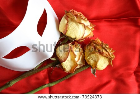 White venetian mask and three dry roses on red cloth background