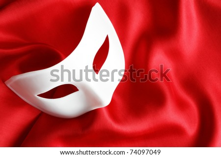 White venetian mask lying on red silk background - stock photo