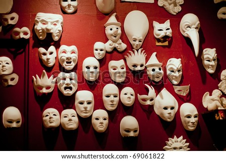 White Venice masks on the red wall - stock photo