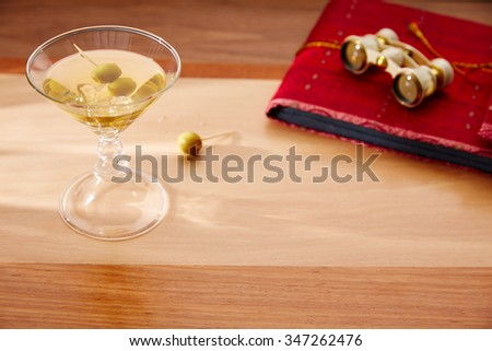 white vermouth cocktail with vintage binoculars on red folder - stock photo