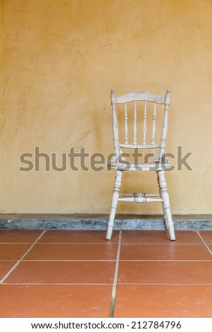white Vintage chair near yellow old wall
