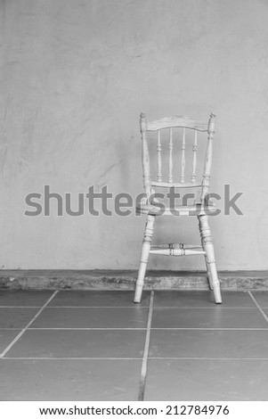 white Vintage chair near yellow old wall BW - stock photo