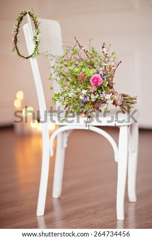White vintage chair with candle and flowers bouquet near white wall. - stock photo