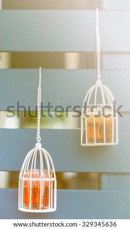 white vintage decoration : Vintage birdcage hanging on wood background, white candles inside - stock photo