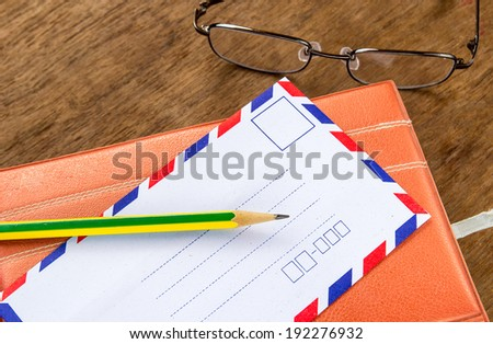 White vintage envelope, pencils, notebook and glasses on a wood floor - stock photo