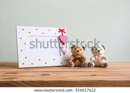 White vintage photo frame with red heart and teddy bear on wooden table over wall grunge background, Valentine day concept. - stock photo