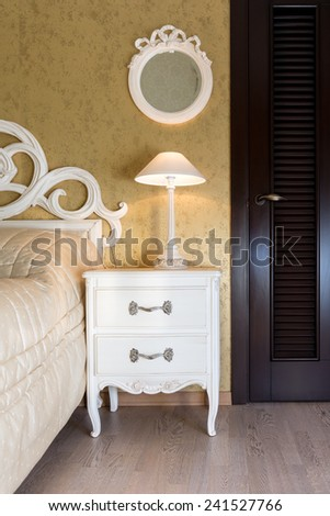 White vintage style nightstand with a lamp in a bedroom - stock photo