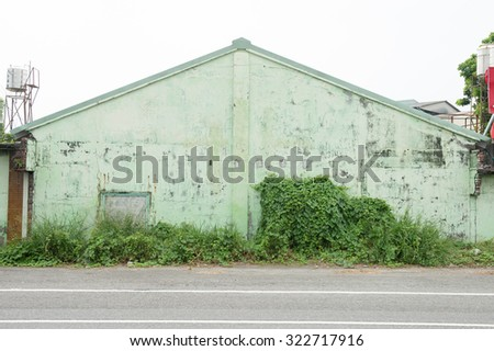 White wall background with green grass - stock photo