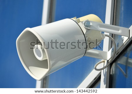 White wall loudspeaker on a glass facade of modern building