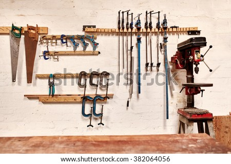 White wall of a woodwork workshop with hand tools hanging in neat rows, a well used drill press on one side and a wooden work bench in the foreground - stock photo