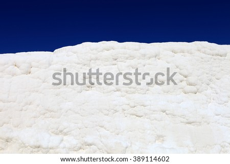 White wall on travertines, textured background at Pamukkale reserve. Natural travertine pools and terraces in Pamukkale resort. Pamukkale or cotton castle, Turkey. - stock photo