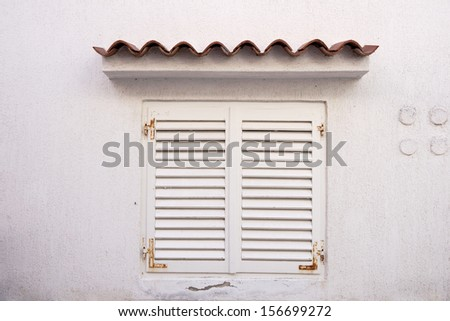 White wall with white shutters and a small roof above