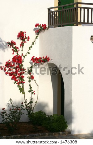 White wash stone house with arch door entrance and balcony, bougainvillea growing by the wall. - stock photo