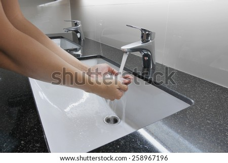 white washbasin and faucet on granite counter with hand washing - stock photo
