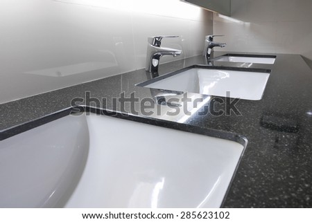 white washbasins and faucet on granite counter in restroom - stock photo