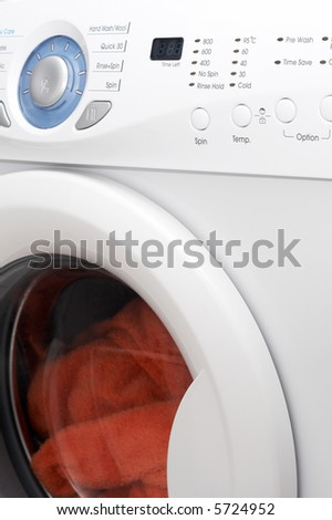 White washing machine with orange towels inside - stock photo
