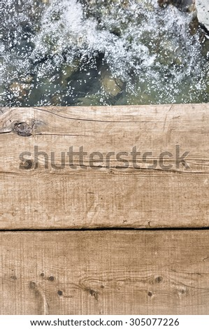 White water passing under a wooden footbridge - stock photo