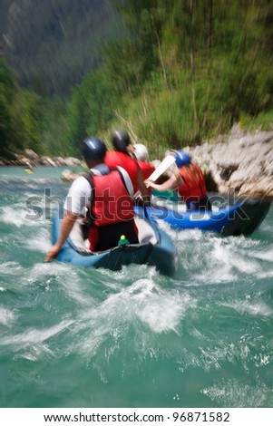 white water rafting (motion blur is used to convey rapid flow of the river/movement of the raft boat) - stock photo