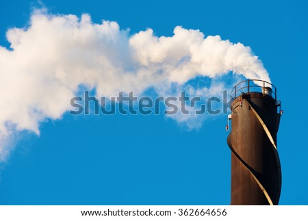 White, water rich smoke comes out of a tall chimney against a clear blue sky. Chimney has red position lights and spiraling vortex dampeners. Copy space in sky. - stock photo