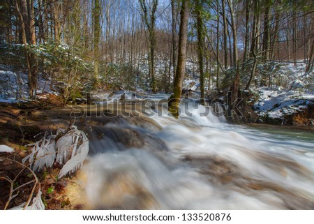 White water river and waterfalls flowing in the mountains in early spring - stock photo