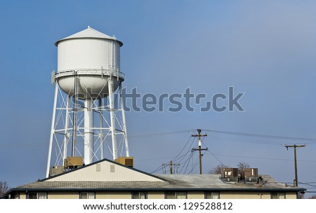 White water tower in the city - stock photo