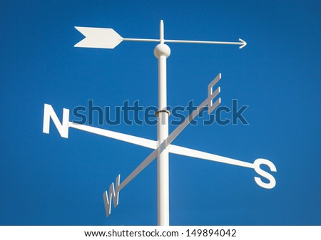 White Weathervane Against a Radiant Blue Sky