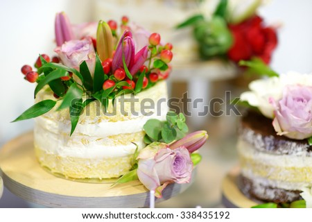 White wedding cake decorated with natural flowers - stock photo