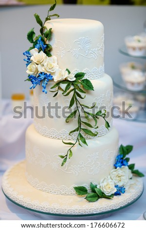 White wedding cake decorated with sugar flowers - stock photo