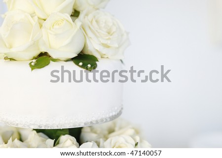 White wedding cake with real roses decorations - stock photo